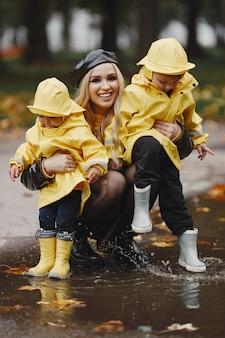 雨の公園の家族。レインコートを着た子供たち。子供を持つ母。黒いコートを着た女性。