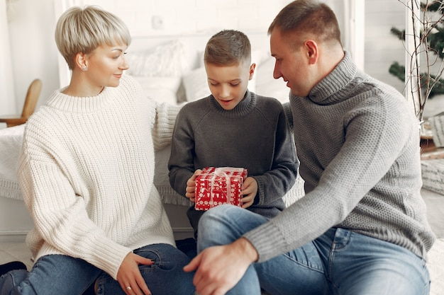 Семья в комнате. маленький мальчик возле рождественского украшения. мать с отцом с сыном