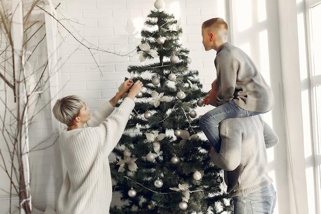 방에있는 가족. 크리스마스 장식 근처 작은 소년. 아들과 아버지와 어머니