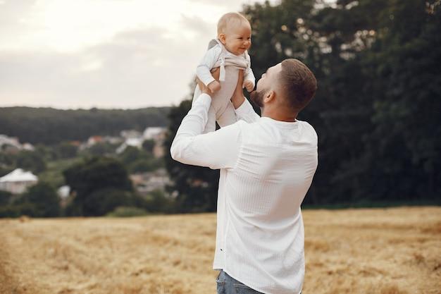 Семья в летнем поле. отец в белой рубашке. милая новорожденная дочь.