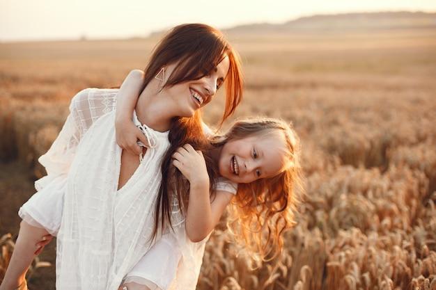 夏の畑で家族。官能的な写真。かわいい女の子。白いドレスを着た女性。