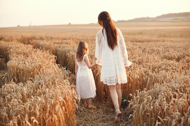 여름 필드에서 가족입니다. 관능적 인 사진. 귀여운 작은 소녀. 흰 드레스에 여자입니다.