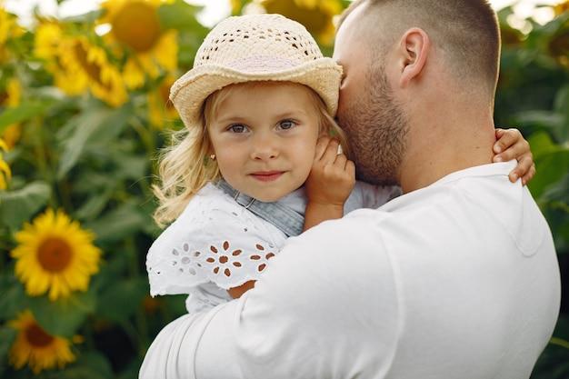 ひまわりと夏の畑で家族。白いシャツの父。かわいい子。