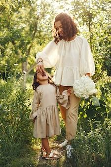 夏の庭で家族。官能的な写真。かわいい女の子。花束を持つ女性。