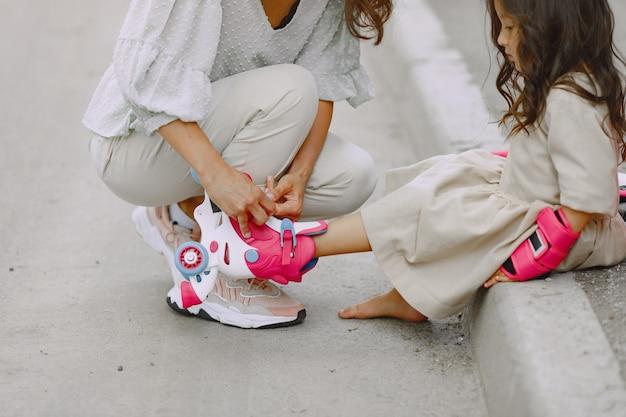 Семья в летнем парке. мать в кофточке. маленькая девочка с роликом.