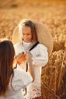 麦畑の家族。白いドレスを着た女性。麦わら帽子の少女。