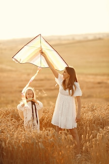 Семья в пшеничном поле. женщина в белом платье. маленький ребенок с воздушным змеем.