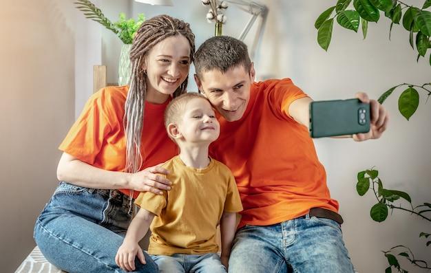 Семья в яркой одежде позирует перед камерой мобильного телефона для фото или удаленного общения