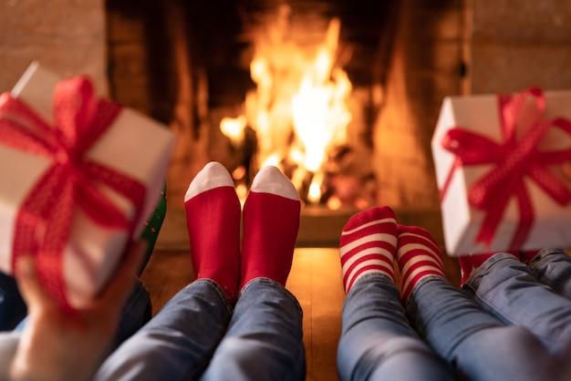 벽난로 근처에서 크리스마스 양말을 신은 가족 어머니 아버지와 아이들이 함께 즐거운 시간을 보내고 있습니다.