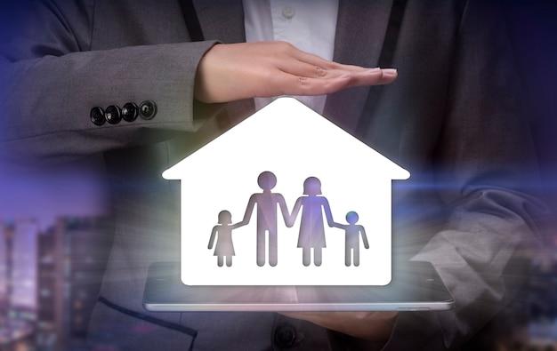 ケアと保護を備えたカップ状の手にある家族金融保険の概念住宅ローン
