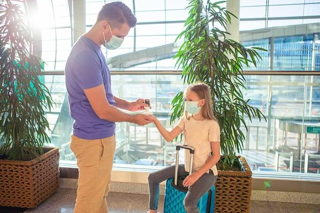 空港のフェイスマスクの家族。父と子は、コロナウイルスとインフルエンザの発生時にフェイスマスクを着用します。ウイルスと病気の保護のための公共の場所での手指消毒剤