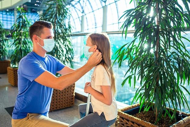空港のフェイスマスクの家族。父と子は、コロナウイルスとインフルエンザの発生時にフェイスマスクを着用します。コロナウイルスとグリップに対する保護
