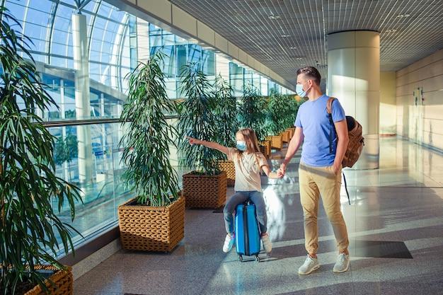 공항에서 얼굴 마스크에 가족. 아버지와 아이는 코로나 바이러스와 독감 발생시 안면 마스크를 착용합니다. 코로나 바이러스 및 그립으로부터 보호