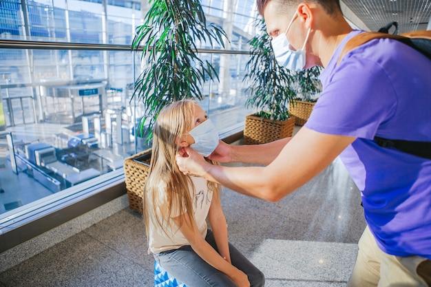 Семья в маске в аэропорту. отец и ребенок носят маски во время вспышки коронавируса и гриппа