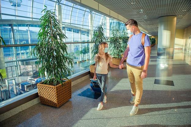 공항에서 얼굴 마스크에 가족. 아버지와 딸이 코로나 바이러스 및 그립 동안 의료용 마스크를 착용