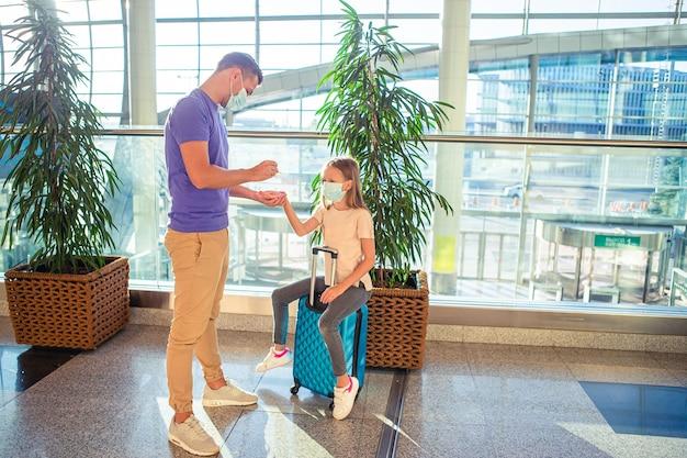 空港でフェイスマスクの家族。ウイルスや病気から保護するための公共の場所での手指消毒剤