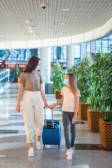 空港のフェイスマスクの家族。母親と幼い子供は、コロナウイルスとインフルエンザの発生中にフェイスマスクを着用します。コロナウイルスに対する保護