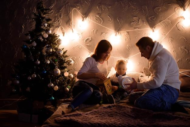 크리스마스 트리 앞의 가족, 행복한 엄마, 아빠가 마법의 밤에 아기를 안고 있습니다.