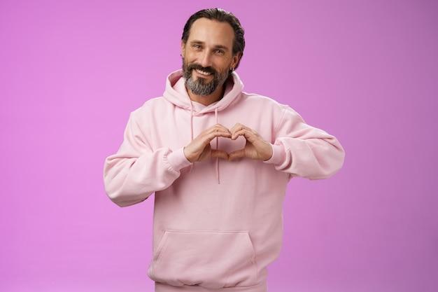心の中の家族。ピンクのパーカーの肖像画の素敵なハンサムなロマンチックなひげを生やした男は、情熱的に見えるカメラは、ロマンチックな同情の態度、紫色の背景を表現するかわいい笑顔の愛のジェスチャーを示しています。