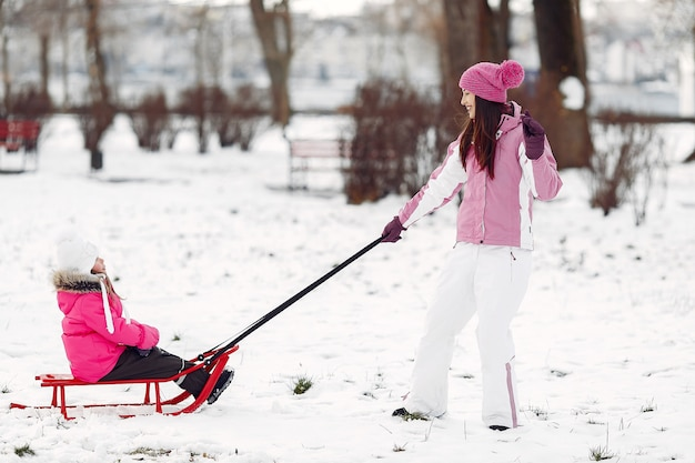 家族のクリスマス休暇にニットの冬の帽子をかぶった家族。公園の女性と少女。そりで遊ぶ人。