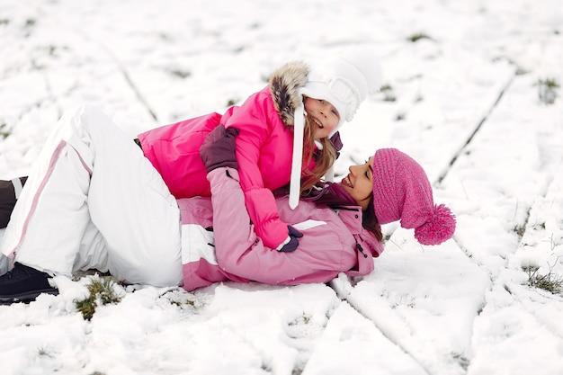 家族のクリスマス休暇にニットの冬の帽子をかぶった家族。公園の女性と少女。遊んでいる人。