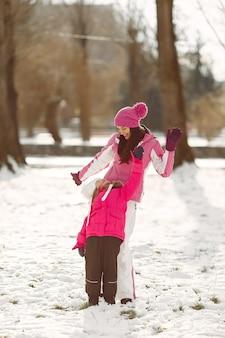Семья в вязаных зимних шапках на семейных рождественских каникулах. женщина и маленькая девочка в парке. люди играют.