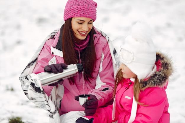 家族のクリスマス休暇にニットの冬の帽子をかぶった家族。公園の女性と少女。人々は魔法瓶を持っています。