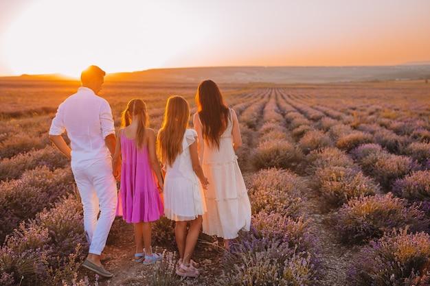白いドレスと帽子で日没時のラベンダーの花畑の家族