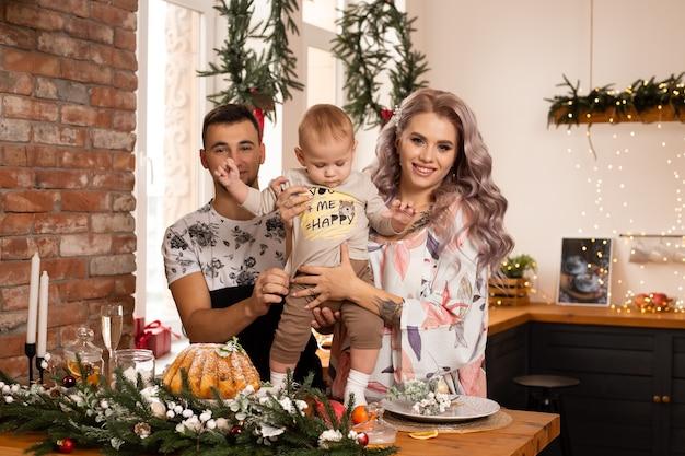 素敵な装飾が施されたクリスマスツリーの近くのキッチンで、クリスマスの魔法を楽しんでいる家族。