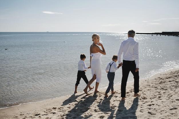 暖かい服装で家族は暖かい晴れた日に砂浜で裸足で歩いています。
