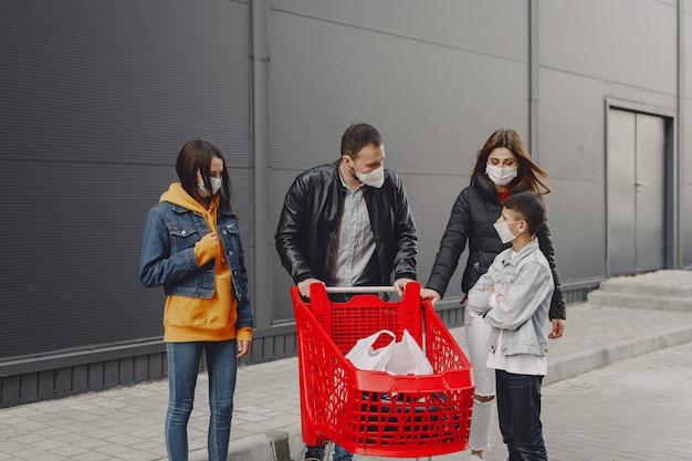 Семья в защитных масках с покупками