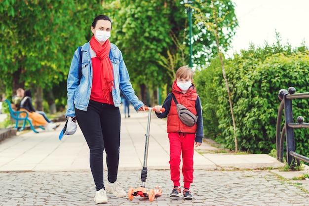 Семья в масках безопасности на открытом воздухе. езда мальчика на скутере в парке. мальчик носит медицинскую маску.
