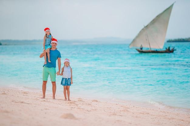 Семья в шляпах санты на тропическом пляже празднует рождественские каникулы