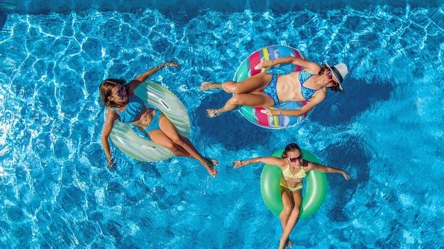 上からスイミングプールの空中ドローンビューで家族、幸せな母と子供はインフレータブルリングドーナツで泳ぐし、家族での休暇、リゾートで熱帯の休日に水で楽しい