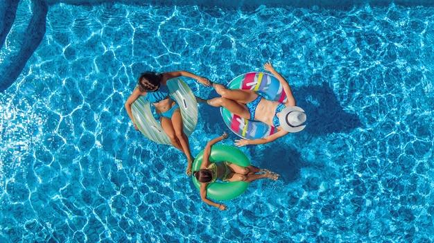 위에서 수영장 공중 무인 항공기보기 가족, 행복한 어머니와 아이들은 풍선 링 도넛에서 수영과 가족 휴가, 리조트의 열대 휴가에 물에서 재미를