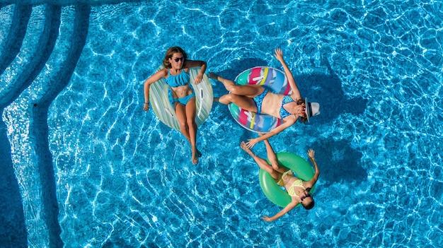 上からプールの空撮で家族、幸せな母と子供はインフレータブルリングドーナツで泳ぐし、家族での休暇、リゾートで熱帯の休日に水で楽しい