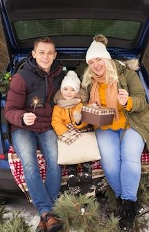Семья в машине празднует рождество на улице зимой