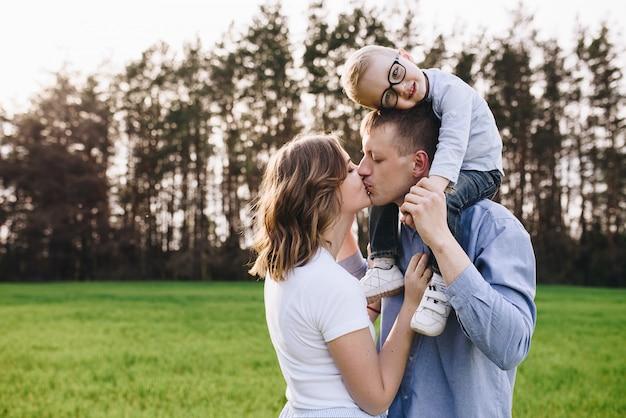소풍에서 숲에서 가족입니다. 맑고 푸른 잔디에 앉으십시오. 파란 옷. 엄마와 아빠는 아들과 놀고, 포옹하고 미소 짓습니다. 안경 아이.