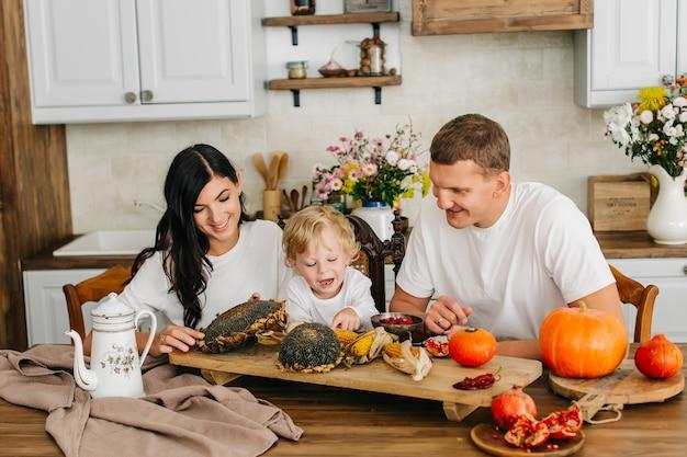 台所で家族。彼女の幼い息子を持つ美しい母親。収穫かぼちゃ、ひまわり、りんごがたくさん。
