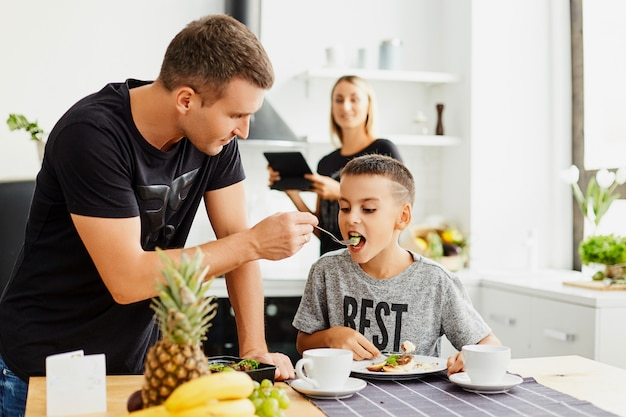 Семья на кухне ест еду