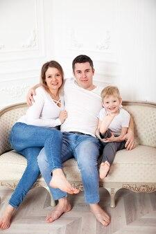 Семья в белом и джинсах на светлом диване у белой стены