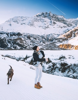 背景に山がある冬の雪に覆われた田園地帯の家族オーストリアの冬の山のハイキング