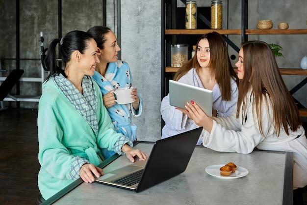가족은 여성이 드레싱 가운을 입고 테이블에 앉아 회의를 하는 전자 기기를 사용하여 아침 식사에서 무언가에 대해 논의하고 있습니다.
