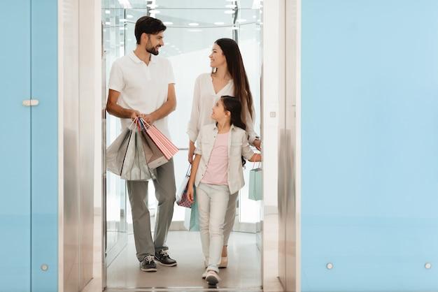 Семья выходит из торгового центра с сумками, полными покупок.