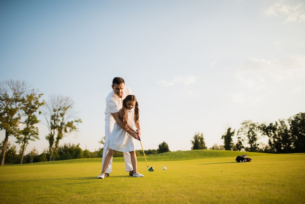Family is golfing sport hobby father teaches kid.