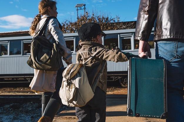家族は駅で旅行中です
