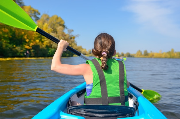 Family kayaking, child paddling in kayak on river canoe tour, kid on active autumn weekend and vacation
