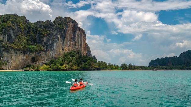 海での家族のカヤック、島の近くの熱帯の海のカヌーツアーでカヤックを漕ぐ母と娘、タイ、クラビで子供たちと楽しく活発な休暇を過ごす