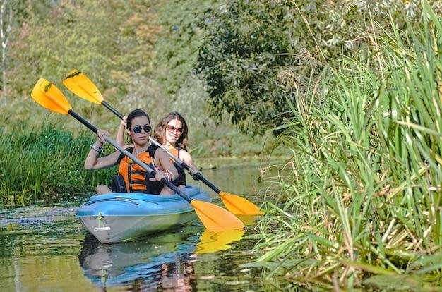 Семья каякинг, мать и дочь, гребля на каяке на речном каноэ, развлекается