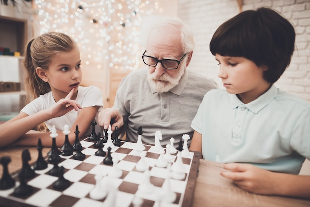 Family kids play chess at home people thinking.